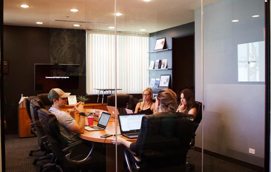 första jobb, fyra personer i ett arbetsrum framför datorer