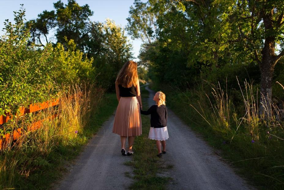 barnpassning ung tjej med ett barn som håller hand på en stig