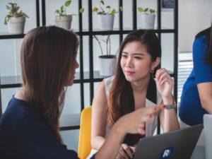 Två personer som diskuterar anställningsstatistik gällandeextroverta personer på positioner som vanligtvis är jobb för introverta