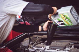 En mekaniker, ett bra jobb för introverta personer, som fyller på olja i ett fordon
