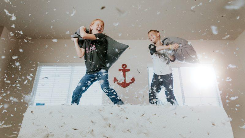 Två barn som bråkar med kuddar