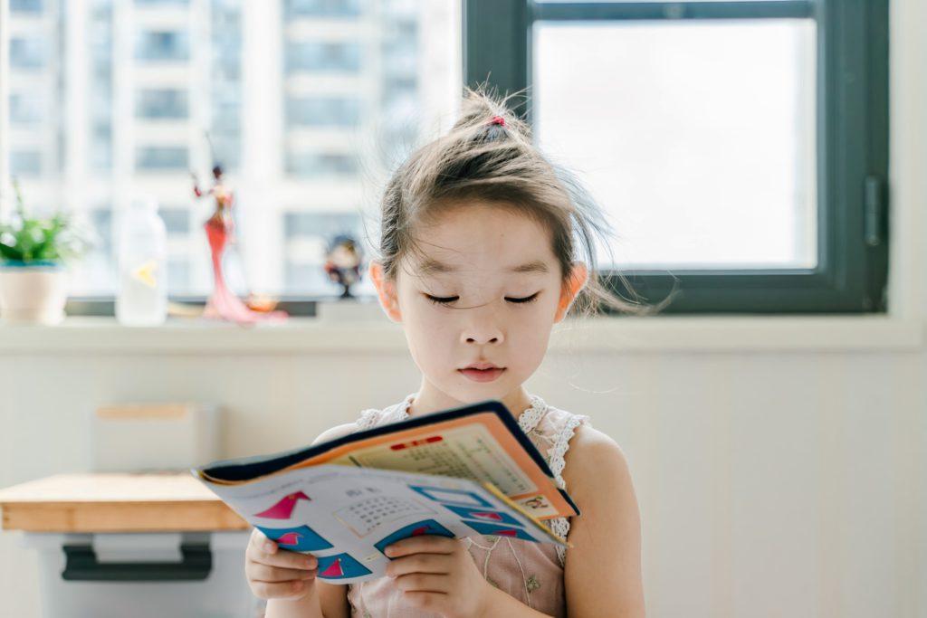En liten flicka som läser en tidning