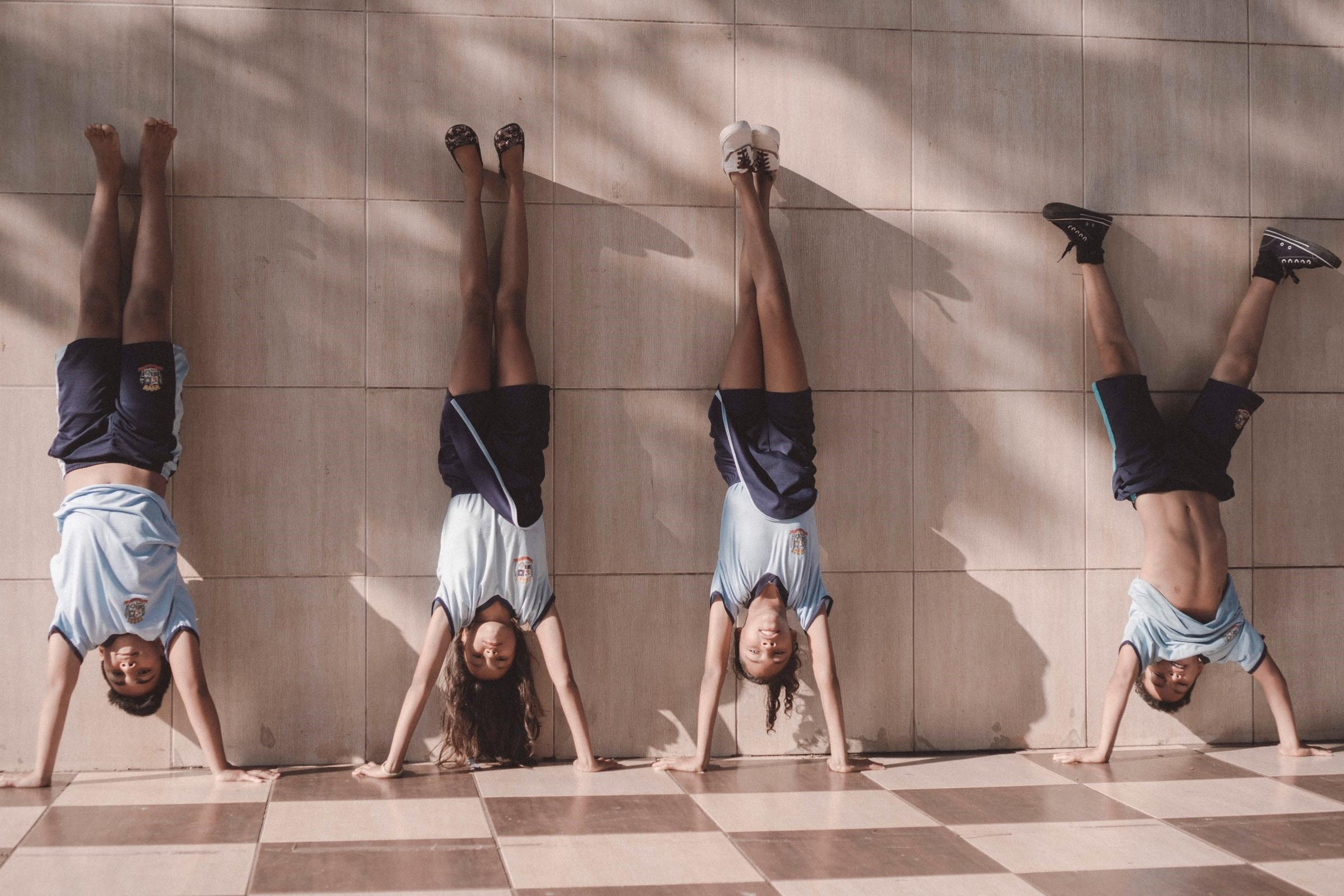 4 barn som övar handstående gymnastik under rasten
