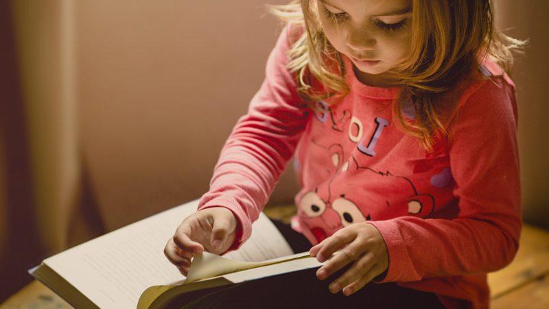 Liten flicka som läser för kognitiv utveckling