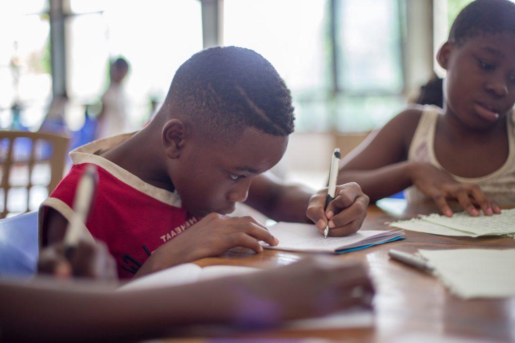 Liten pojke som skriver i skolan att utvecklas kognitivt