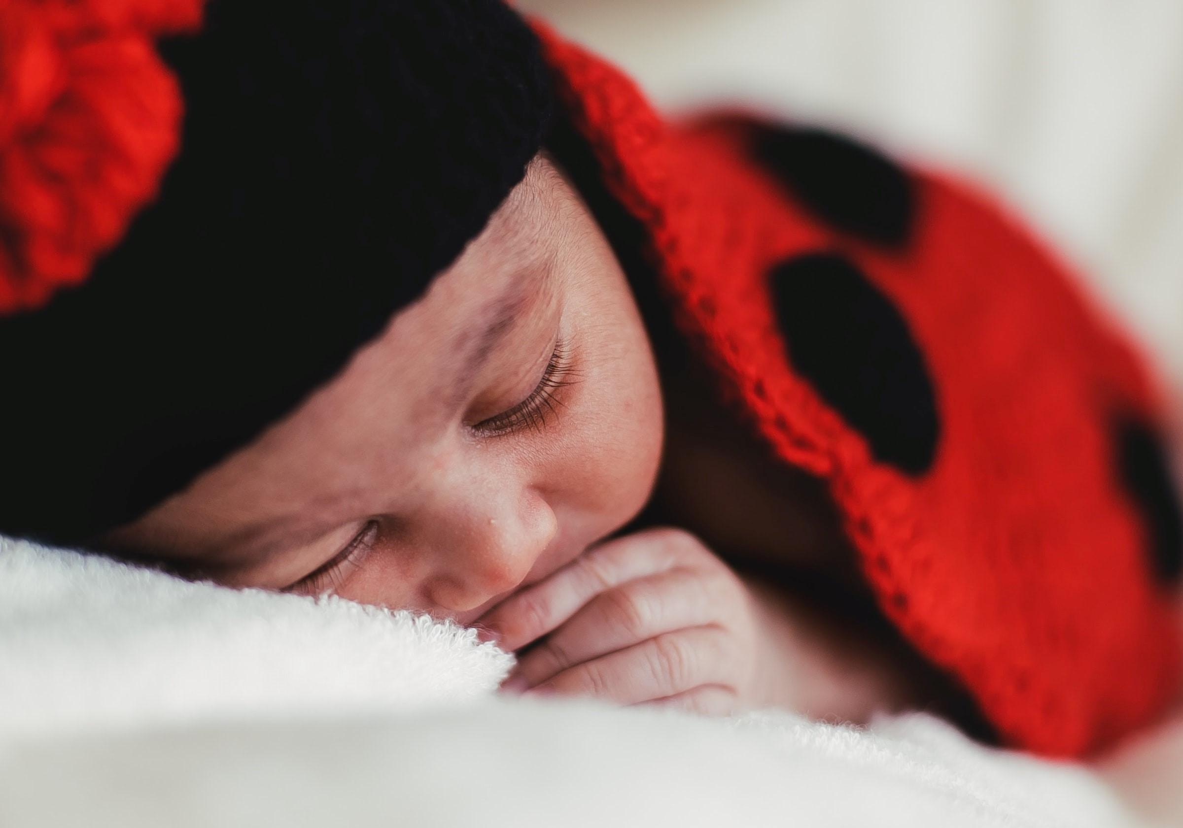 Ett barn som sover i fina nyckelpigemönster