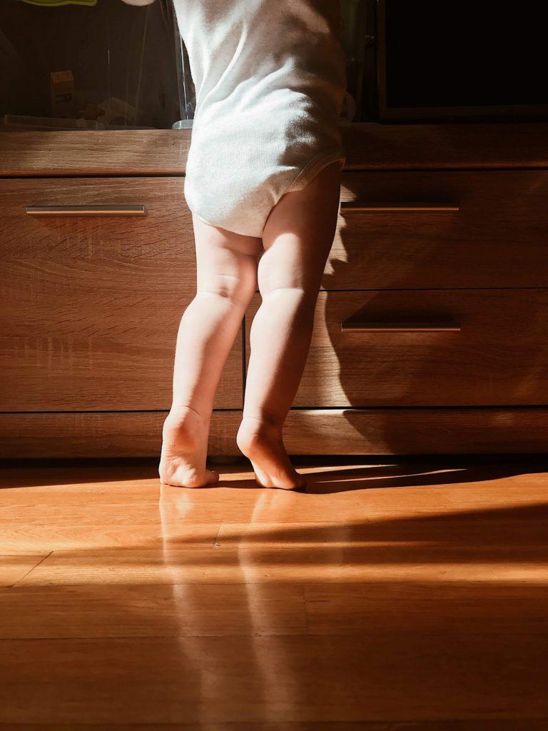 Ett barn som står på tå för att nå