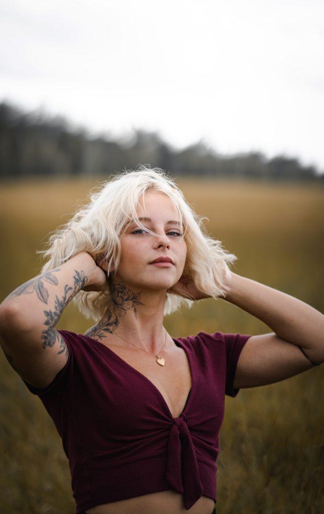 En tjej på ett fält som tar sig om håret